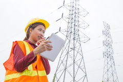 Woman Engineering working on High-voltage tower Stock Photo