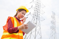 Woman Engineering working on High-voltage tower Stock Image