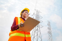 Woman Engineering working on High-voltage tower. Walkie-talkie on hand Royalty Free Stock Photos