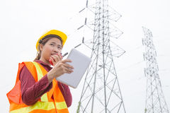 Woman Engineering working on High-voltage tower. Walkie-talkie on hand Stock Photo