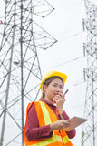 Woman Engineering working on High-voltage tower. Walkie-talkie on hand Stock Image