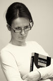 Woman with English book. Black and white portrait of young woman with business English book, studio background Stock Images