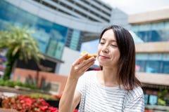 Woman enjoy egg tart at outdoor Stock Photography