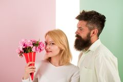 Woman enjoy fragrance bouquet flowers. Couple in love happy celebrate anniversary. Man with beard takes care about. Girlfriend happiness. Lady likes flower stock image
