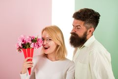 Woman enjoy fragrance bouquet flowers. Man with beard takes care about girlfriend happiness. Lady likes flower husband. Gifted her. Flowers delivery concept stock image