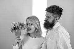 Woman enjoy fragrance bouquet flowers. Man with beard takes care about girlfriend happiness. Lady likes flower husband stock photography