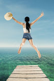 Woman enjoy freedom by jump at pier Royalty Free Stock Photos