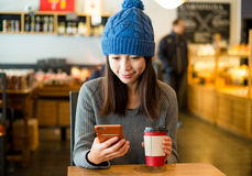 Woman enjoy her coffee and look at mobile phone Royalty Free Stock Photography