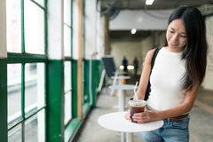 Woman enjoy her iced coffee at open air coffee shop. Asian young woman Royalty Free Stock Images