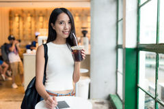Woman enjoy her iced coffee at open air coffee shop in Hong Kong. Asian young woman Stock Photography