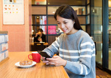 Woman enjoy her morning breakfast with her cellphone Royalty Free Stock Photography