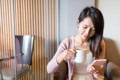 Woman enjoy her morning coffee and using cellphone Stock Photos