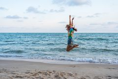 Woman enjoy and jumping on sea beach royalty free stock photo