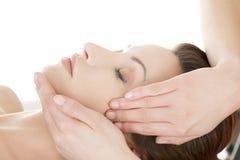 Woman enjoy receiving face massage. Beautiful young relaxed woman enjoy receiving face massage at spa saloon Stock Images