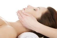 Woman enjoy receiving face massage. Beautiful young relaxed woman enjoy receiving face massage at spa saloon Stock Photo