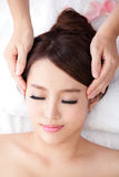 Woman enjoy receiving face massage at spa with roses. Beautiful young woman enjoy receiving face massage at spa with roses, she is very relaxed , asian beauty Royalty Free Stock Photo
