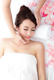 Woman enjoy receiving face massage at spa with roses Stock Photo