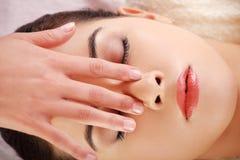 Woman enjoy receiving face massage at spa saloon. Beautiful young relaxed woman enjoy receiving face massage at spa saloon Royalty Free Stock Images