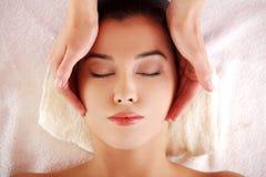 Woman enjoy receiving face massage at spa saloon. Beautiful young relaxed woman enjoy receiving face massage at spa saloon Stock Photo