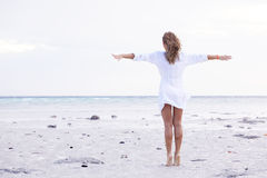 Woman enjoy sea beach. Barefoot woman in white shirt enjoy sea wind on sandy beach Royalty Free Stock Photo