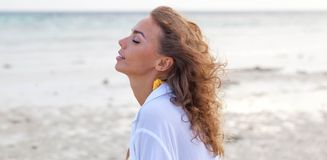 Woman enjoy sea scent. Attractive woman enjoy sea scent smelling wind with closed eyes on sea beach Stock Photography