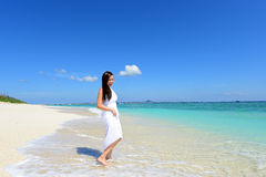 Woman enjoy the sun. Young Asian woman on the beach enjoy sunlight Royalty Free Stock Image