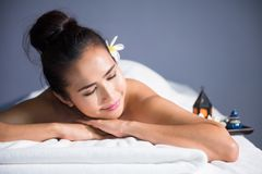 Woman enjoy thai oil massage. Portrait of young happy Asian beautiful woman relax in spa. Body care treatment. Cute girl having massage at back by professional stock photos