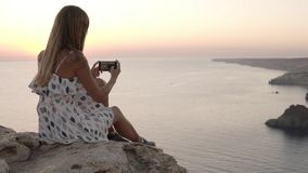 Woman enjoy the view of the sea during sunset time and taking photo on cellphone. Longhaired girl sitting on the cliff. In bright sundress admiring the time stock video footage
