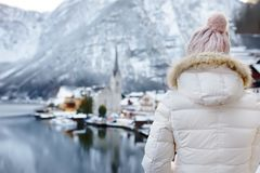 Woman enjoy winter scenic view of village of Hallstatt in the Austrian Alps. Female tourist looking on famous postcard view of Hallstatt royalty free stock image