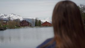 Woman enjoying amazing view over lake and mountains and relaxed on sunny spring day. Rear view. Focus transition. 4k stock footage