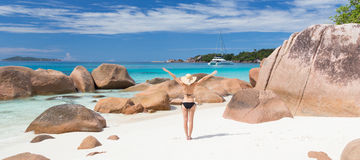 Woman enjoying Anse Lazio picture perfect beach on Praslin Island, Seychelles. Woman arms rised, wearing black bikini and beach hat, enjoying amazing view on royalty free stock photos