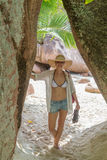 Woman enjoying Anse Lazio picture perfect beach on Praslin Island, Seychelles. Barefooted woman wearing white loose tunic over bikini and beach hat on Anse royalty free stock photos