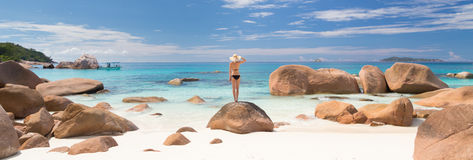 Woman enjoying Anse Lazio picture perfect beach on Praslin Island, Seychelles. Woman wearing black bikini and beach hat, enjoying amazing view on Anse Lazio royalty free stock images