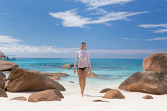 Woman enjoying Anse Lazio picture perfect beach on Praslin Island, Seychelles. Woman wearing stylish bikini and lycra top enjoying swimming and snorkeling at stock images