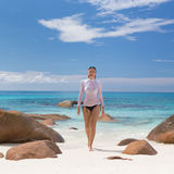 Woman enjoying Anse Lazio picture perfect beach on Praslin Island, Seychelles. Woman wearing stylish bikini and lycra top enjoying swimming and snorkeling at stock image