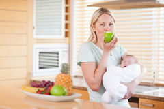 Woman enjoying an apple with her baby on her arms Stock Images