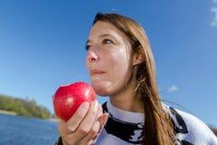 Woman enjoying an apple laughing Stock Photo