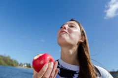 Woman enjoying an apple laughing royalty free stock photography