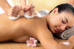 Woman enjoying aromatic pinda massage. Close up portrait of attractive woman enjoying aromatic ayurveda pinda massage on back and shoulder royalty free stock images