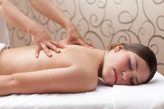 Woman enjoying a back massage in a spa setting Royalty Free Stock Photography
