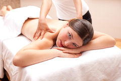 Woman enjoying a back massage in a spa setting Stock Image