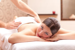 Woman enjoying a back massage in a spa setting Royalty Free Stock Photos