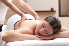 Woman enjoying a back massage in a spa setting Stock Images