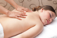 Woman enjoying a back massage in a spa setting Stock Photography