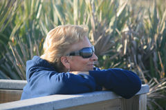 Woman enjoying the beach. Look at the reflection of the seashore, in the woman's sunglasses,while she is enjoying a sunny day at the beach Stock Images
