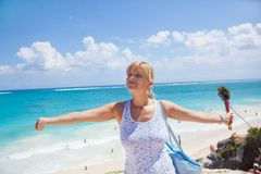 Woman enjoying the beach. Young woman stretching arms on the beach Stock Image