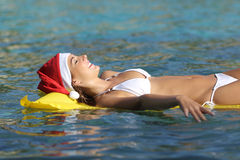 Woman enjoying on the beach on christmas holidays. Floating on a mattress Stock Images