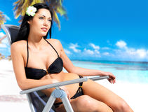 Woman enjoying at beach. Young beautiful woman enjoying at beach sitting on chair Royalty Free Stock Photos