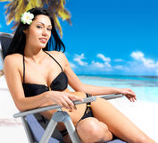 Woman enjoying at beach. Young beautiful woman enjoying at beach sitting on chair Royalty Free Stock Images