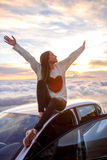 Woman enjoying beautiful cloudscape. Young woman in sweater with heart shape rising hands sitting on the car roof above the clouds on the sunrise. Enjoying Stock Images